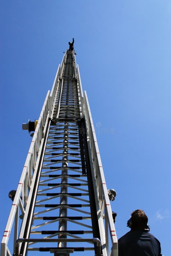 Feuerstrichleiter mit Feuerwehrmann ontop lizenzfreie stockfotos