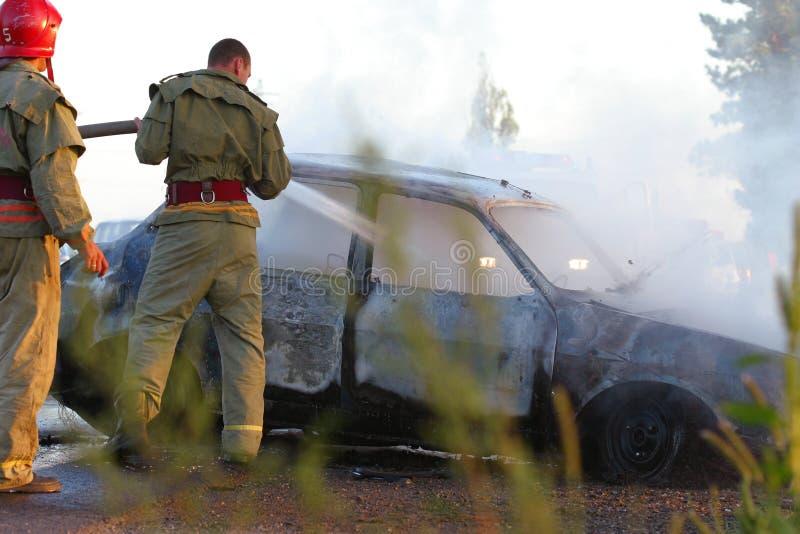 Feuerwehrmänner am Autounfall lizenzfreie stockbilder