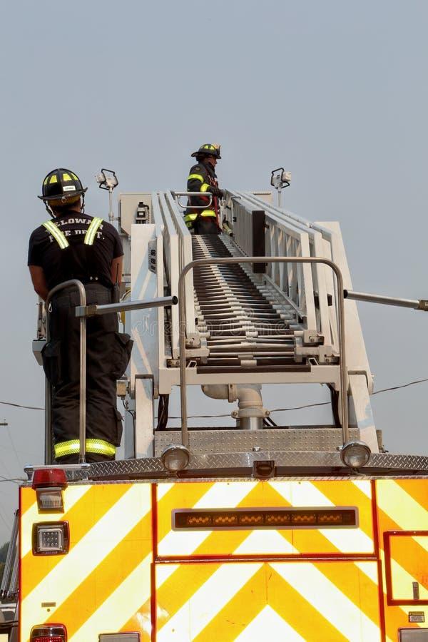 Feuerwehrmänner bei der Arbeit mit Rauche im Hintergrund stockbilder