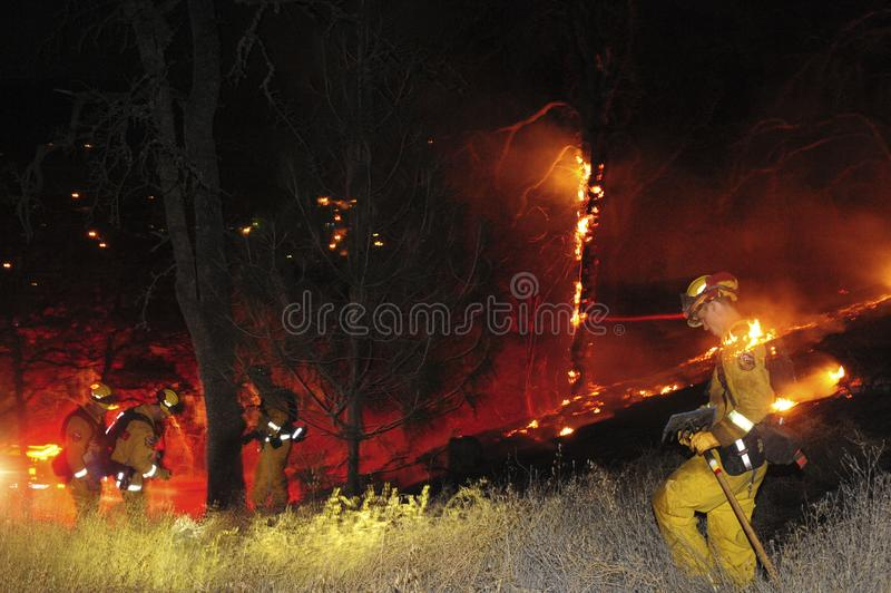 Feuerwehrmänner bei der Arbeit unter einer Wiesenflamme stockfotografie