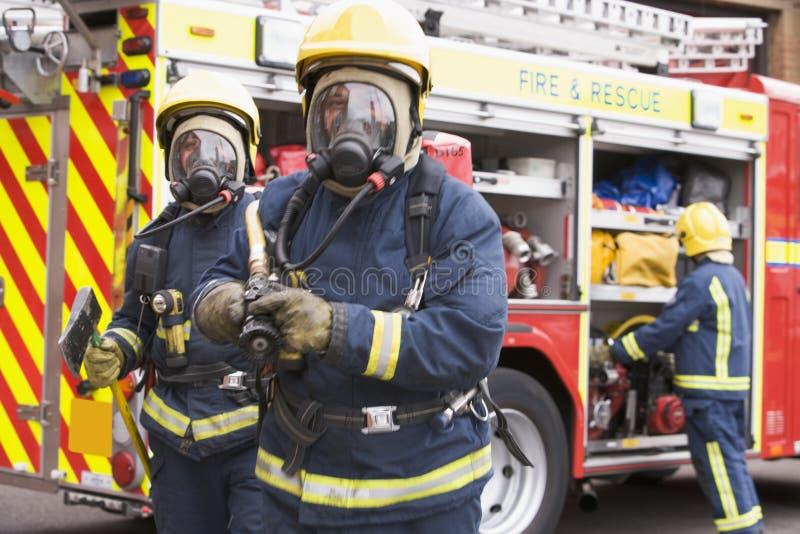 Feuerwehrmänner in der schützenden Arbeitskleidung stockfotos
