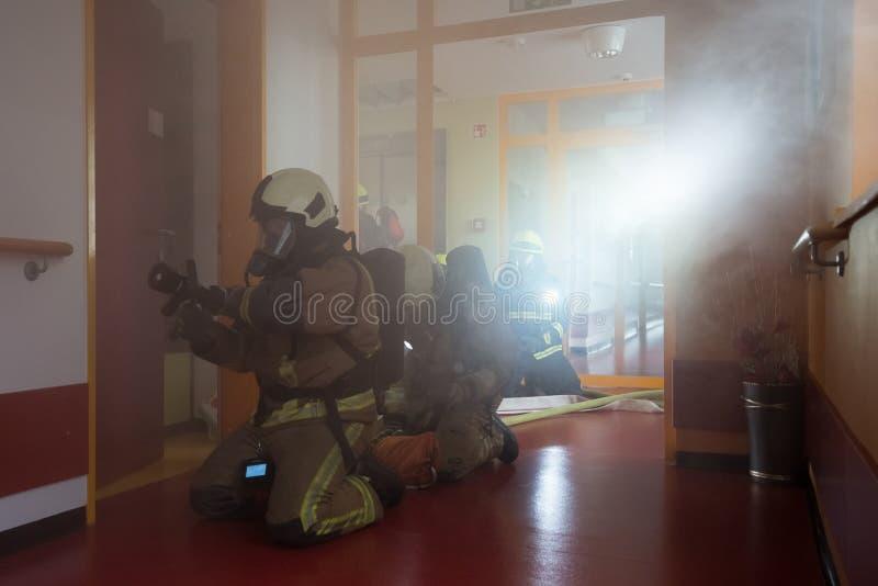 Feuerwehrmänner in der Tätigkeit stockbild