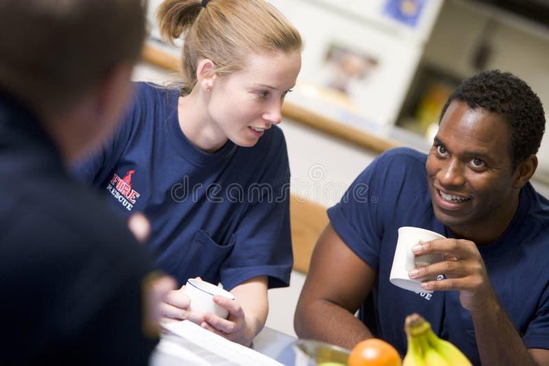Feuerwehrmänner, die in der Personalküche sich entspannen lizenzfreies stockfoto
