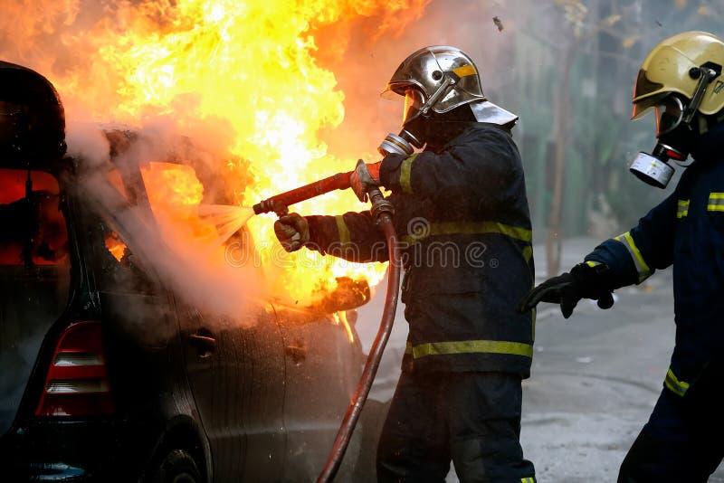 Feuerwehrmänner, die ein loderndes Auto nach einer Explosion kämpfen stockfotos