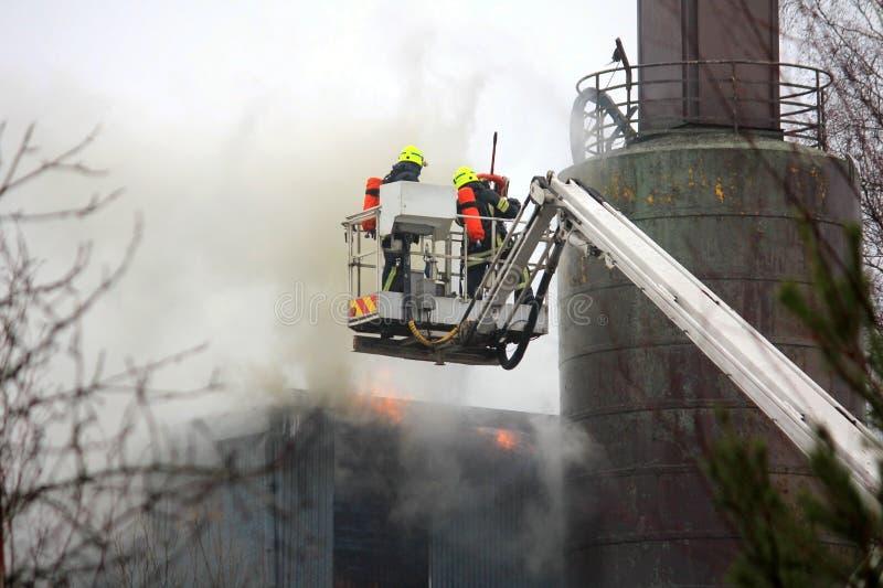 Feuerwehrmänner, die Feuer auf hydraulischem Crane Platform auslöschen stockfotos