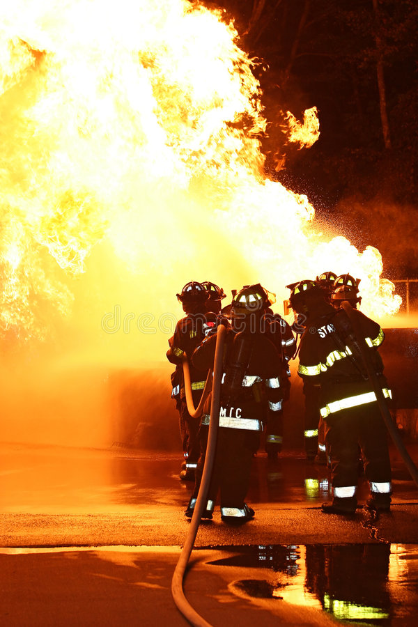 Feuerwehrmänner, die Flames-2 in Angriff nehmen stockbild