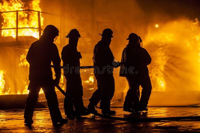 Feuerwehrmänner, die hinunter Feuer mit einem Schlauch bespritzen stockfotos