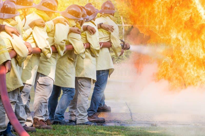 Feuerwehrmänner, die Wasser vom Schlauch für Feuerbekämpfung am Feuerkampf tr verwenden stockfotos