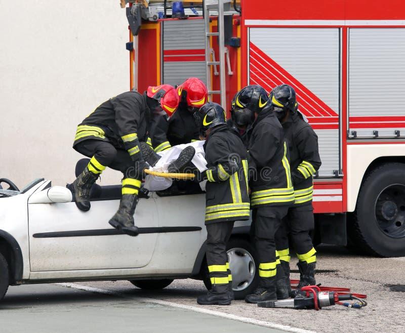 Feuerwehrmänner entlasten verletzt nach Autounfall lizenzfreie stockfotografie