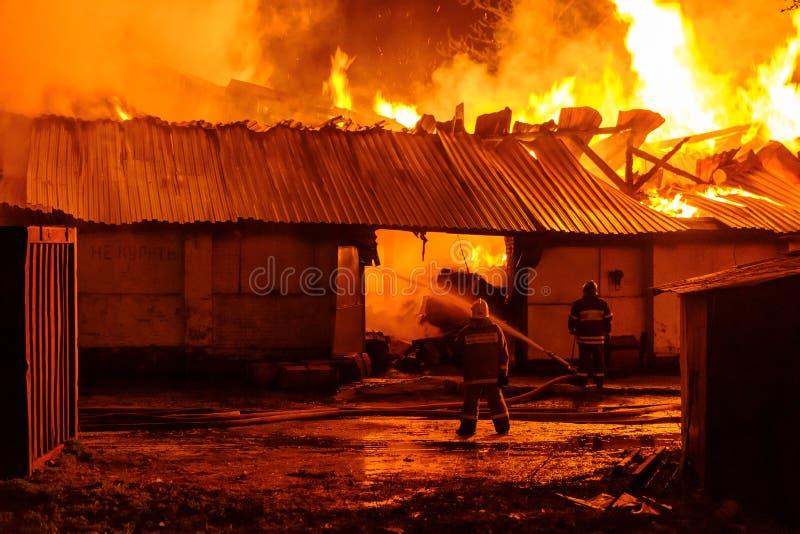 Feuerwehrmänner löschen ein Feuer lizenzfreie stockfotos