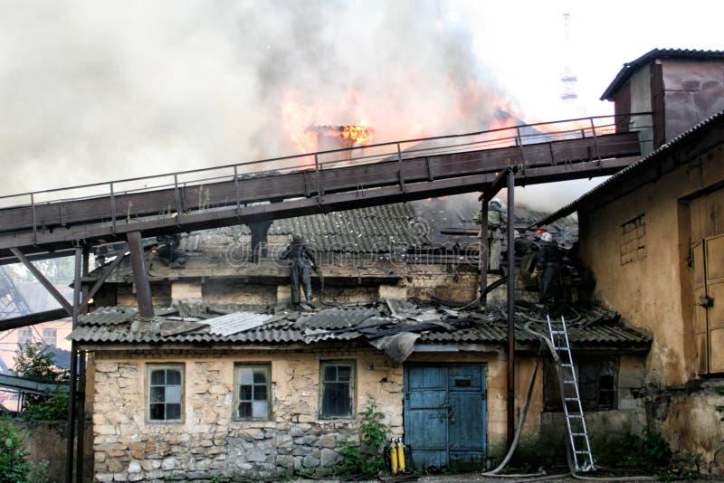 Feuerwehrmänner löschen ein Feuer in einem Apartmenthaus aus stockfotografie