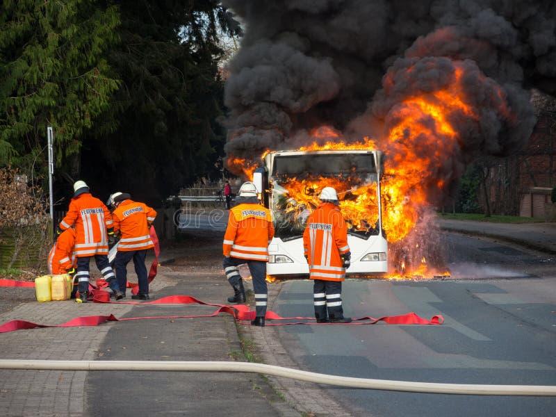Feuerwehrmänner löschen einen brennenden Bus aus lizenzfreie stockfotos