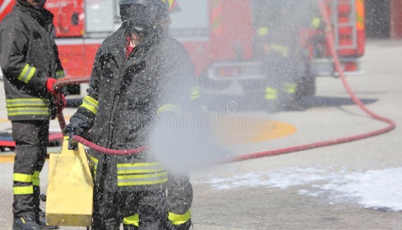 Feuerwehrmänner mit dem Feuerlöscher während einer Übungsstunde stockfotografie