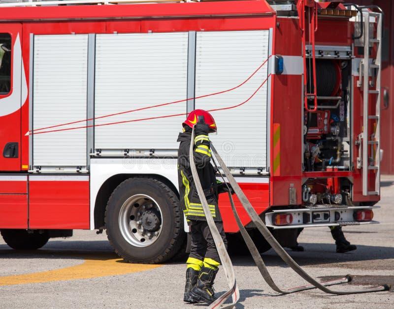 Feuerwehrmänner mit dem Schlauch, zum der Feuer und des firetruc heraus zu setzen lizenzfreie stockfotografie