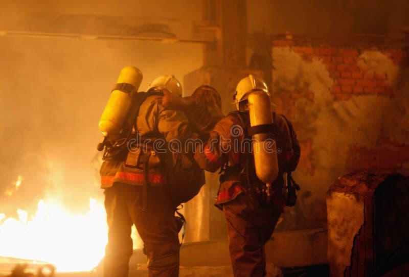 Feuerwehrmänner mit Unfallopfer stockbilder