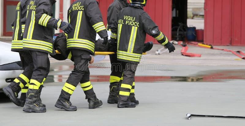 Feuerwehrmänner trugen verletzt weg auf Bahren stockbild