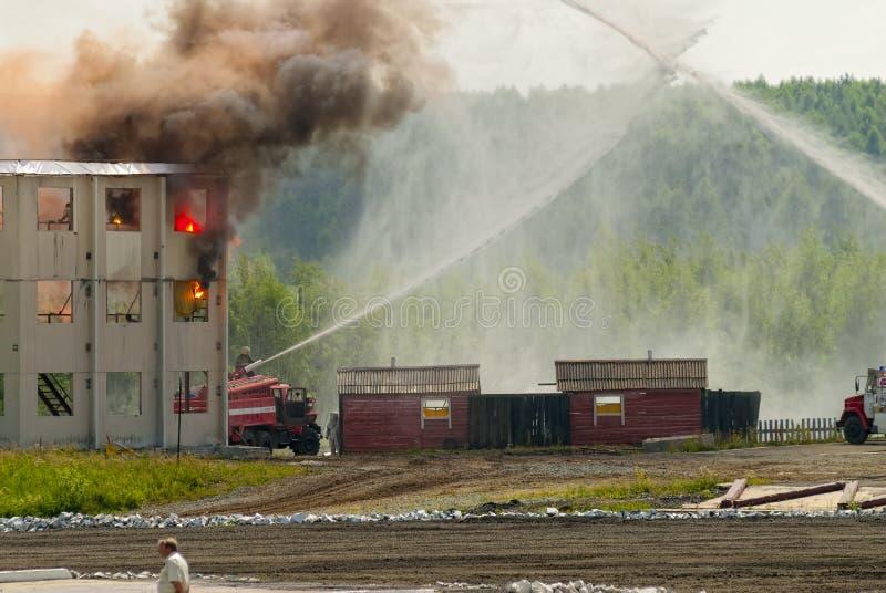 Feuerwehrmänner und Krankenwagenteamarbeit am Feuer lizenzfreies stockfoto