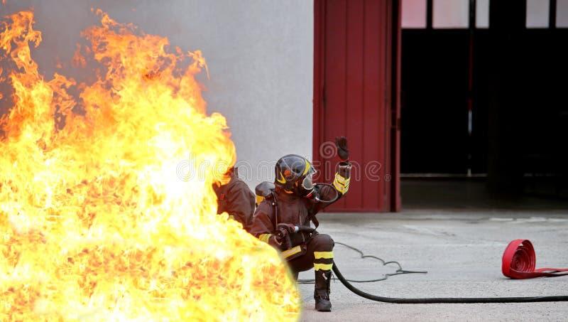 Feuerwehrmänner während der Übung für das feuerlöschende caus lizenzfreie stockbilder