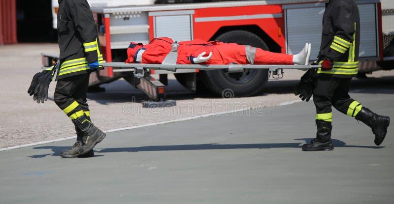 Feuerwehrmänner während der Übung, zu tragen verletzt mit dem s lizenzfreies stockfoto