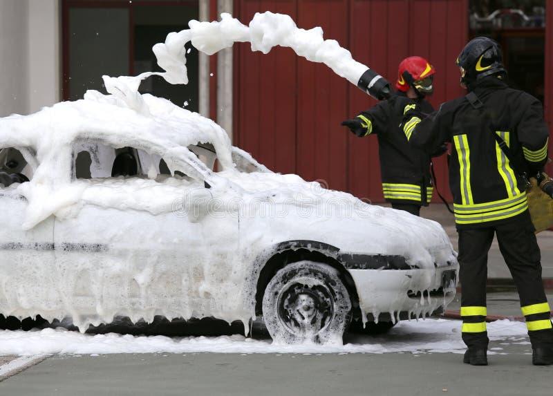 Feuerwehrmänner während der Übung, zum eines Feuers in einem Auto auszulöschen stockbild