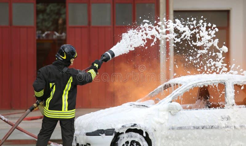 Feuerwehrmänner während der Übung, zum eines Feuers in einem Auto auszulöschen lizenzfreies stockbild
