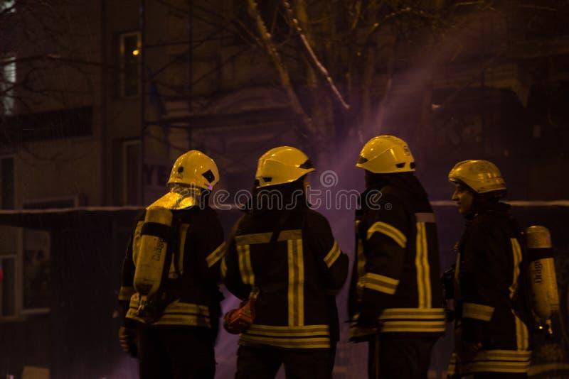 Feuerwehrm?nner bei der Arbeit Ausl?schung des L?schwassers in der Winternacht Feuerturm, Feuerl?schschlauch Kiew, am 20. Januar  lizenzfreie stockbilder