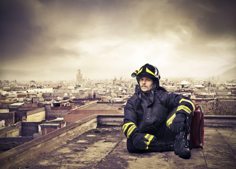 Feuerwehrmann auf einem Stadt-Dach lizenzfreie stockbilder