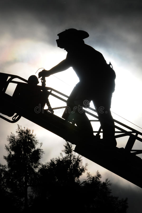 Feuerwehrmann auf Strichleiter stockfotografie