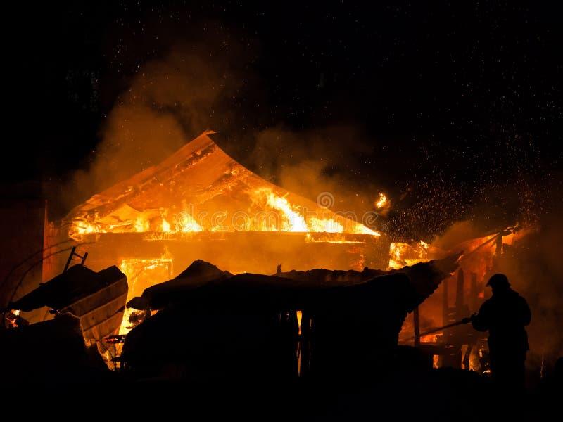 Feuerwehrmann an brennender Feuerflamme auf Holzhausdach lizenzfreies stockfoto