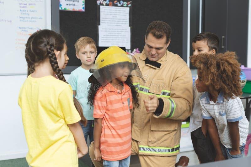 Feuerwehrmann, der auf Schulkinder während eine von ihnen Holdingfeuersturzhelm auf ihrem Kopf einwirkt lizenzfreie stockbilder