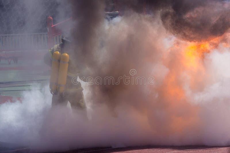 Feuerwehrmann in der Ausrüstung löscht Feuer aus stockfotografie