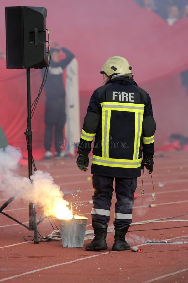 Feuerwehrmann, der Fußball fans& x27 niederlegt; Fackelfeuer lizenzfreies stockfoto
