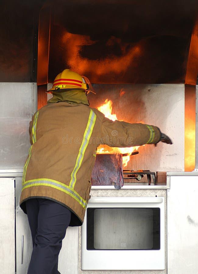 Feuerwehrmann, der heraus Feuer setzt stockbild