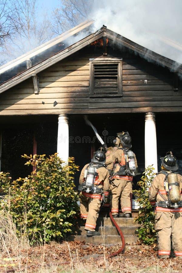 Feuerwehrmann, der heraus Feuer setzt lizenzfreies stockbild