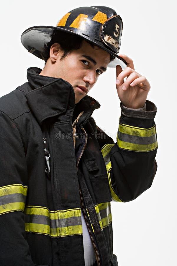 Feuerwehrmann, der seinen Hut spitzt stockfotos