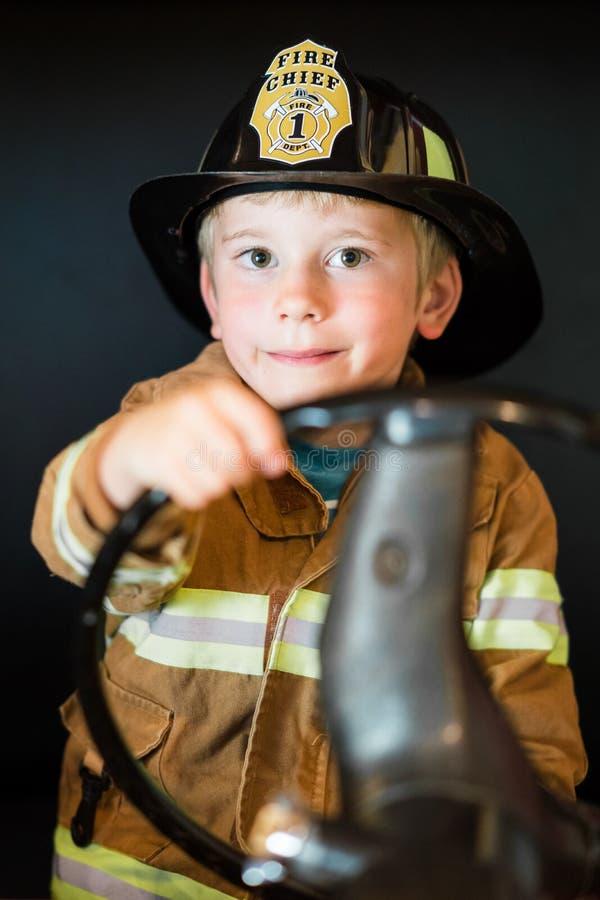 Feuerwehrmann des kleinen Jungen stockbilder