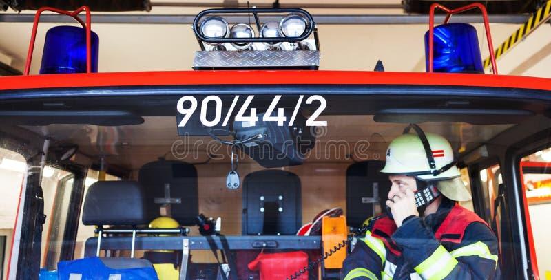 Feuerwehrmann in einem Löschfahrzeug und Funken mit Radiosatz stockbild