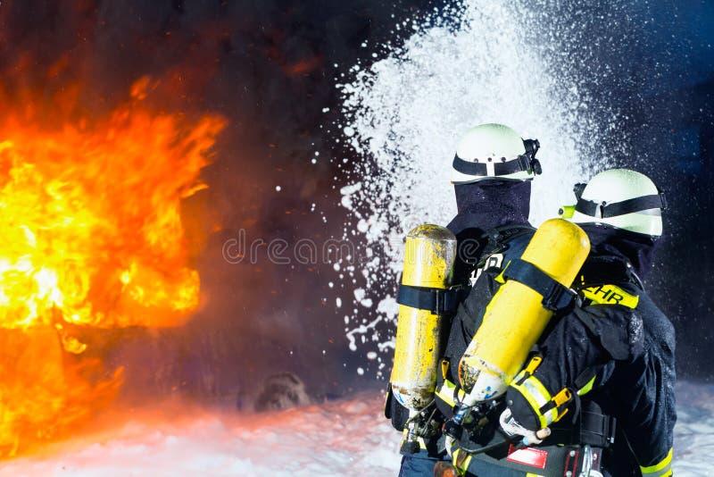 Feuerwehrmann - Feuerwehrmänner, die eine große Flamme löschen stockfotos