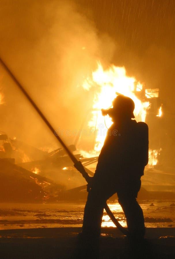 Feuerwehrmann im Schattenbild gegen Flammen lizenzfreie stockfotografie