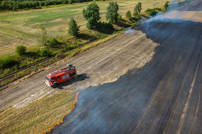 Feuerwehrmann-LKW, der an dem Feld auf Feuer arbeitet stockbilder