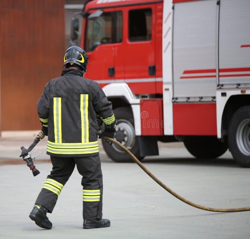 Feuerwehrmann mit einem Schlauch nach der Auslöschung eines Feuers lizenzfreies stockbild