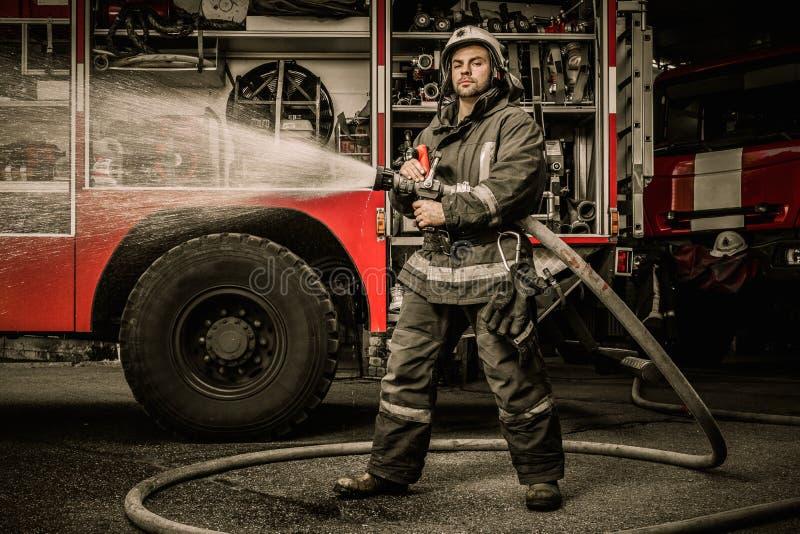 Feuerwehrmann mit Wasserschlauch nahe LKW stockbild