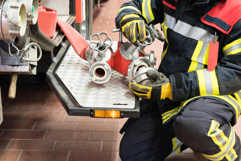 Feuerwehrmann schloss einen Feuerlöschschlauch auf dem Löschfahrzeug an lizenzfreie stockbilder