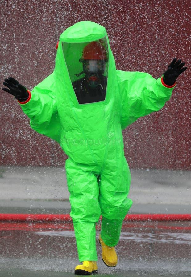 Feuerwehrmann trägt einen Schutzanzug, um ein Feuer auszulöschen, das durch t verursacht wird stockbild