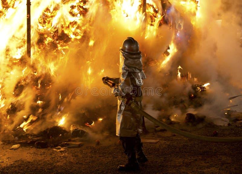 Feuerwehrmann vor einem großen Feuer lizenzfreies stockfoto