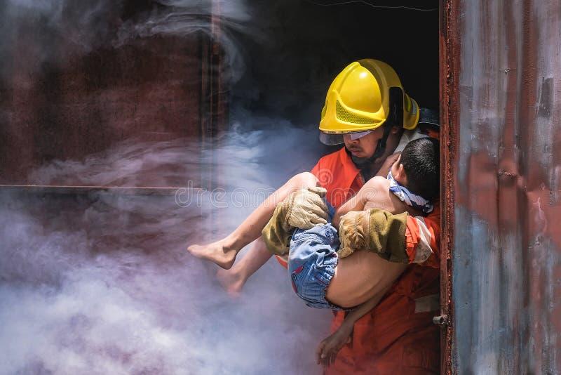 Feuerwehrmannholding-Kinderjunge, zum er in Feuer und Rauch Feuerwehrmännern zu retten, die Jungen zu retten stockbilder