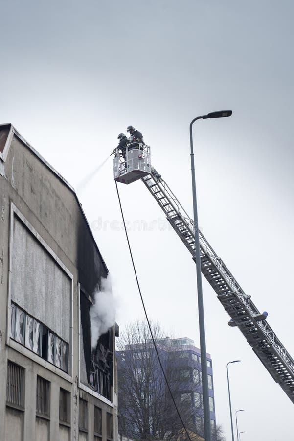 Feuerwehrmannmannschaften, die Lagerhausfeuer kämpfen stockbild