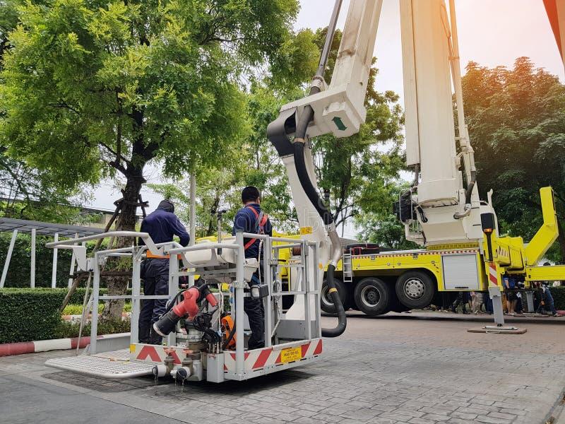 Feuerwehrmannrettungs-Trainingsleute im hohen Gebäude, zum durch die Anwendung des ausgedehnten Leiterkranes des Löschfahrzeugs z stockbild