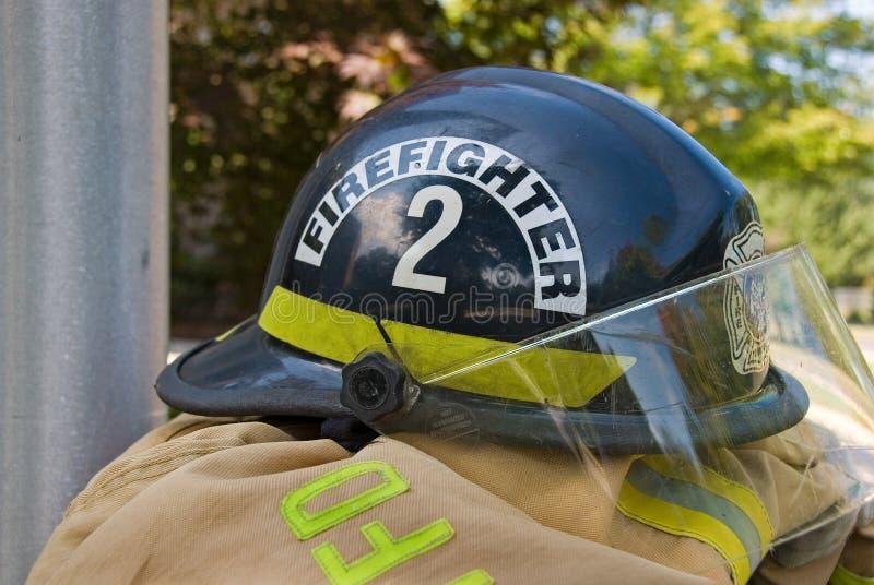 Feuerwehrmannsturzhelm auf Mantel stockfotografie