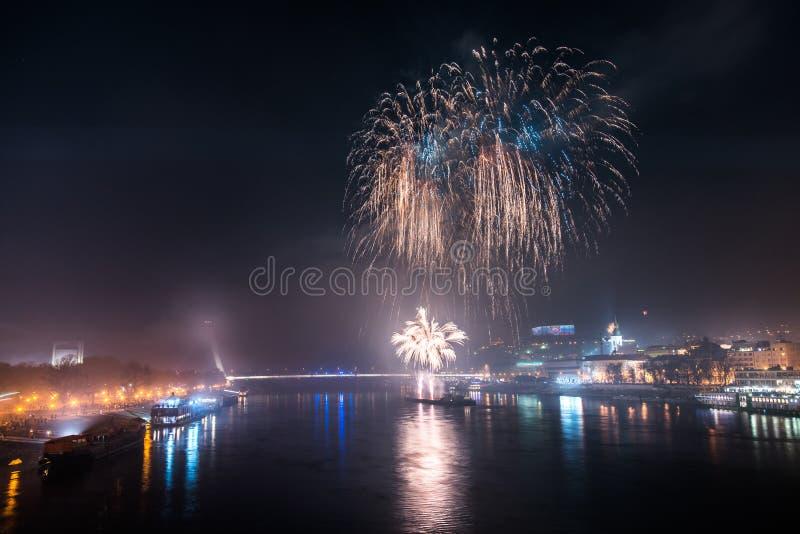 Feuerwerke über dem Fluss in der Stadt stockfotografie